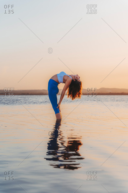 Full length side view of young flexible female in sportswear practicing yoga and doing Standing Backward pose with eyes closed in calm lake water during sunset