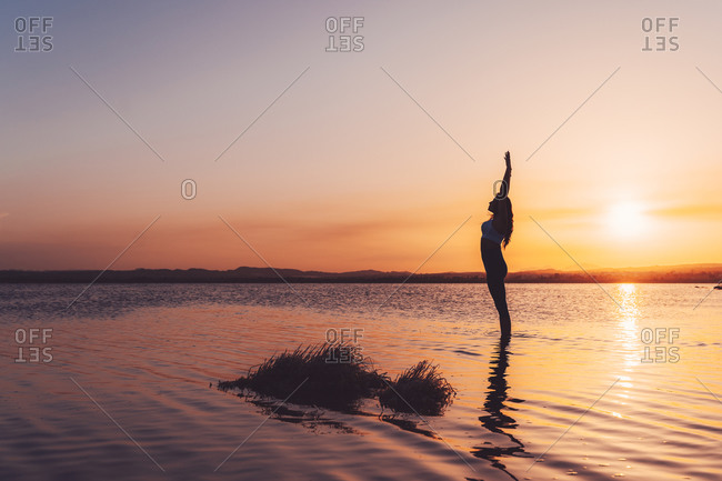Full body side view of unrecognizable slim female in activewear standing in Upward Salute Pose with arms up in lake water while practicing yoga during sunset