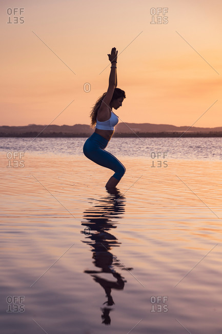 Full length side view of flexible slim female in activewear performing Garudasana pose while practicing yoga alone on lake shore in summer evening