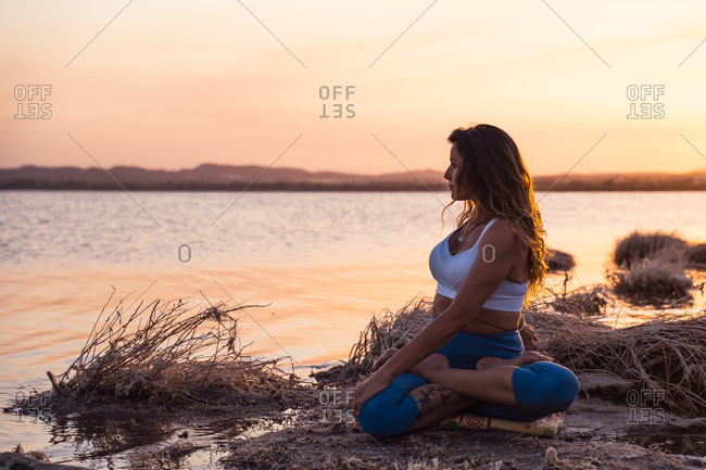 Full length serene young female in sportswear sitting in Revolved Lotus Pose while meditating during yoga practice on lake shore during sunset