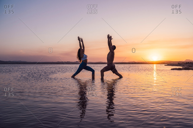 Full length side view of unrecognizable man and woman in sportswear practicing acroyoga and doing Crescent Lunge asana while standing in lake water against sundown sky