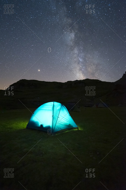 Spectacular view of camping tent placed on meadow in mountainous area under starry sky in long exposure