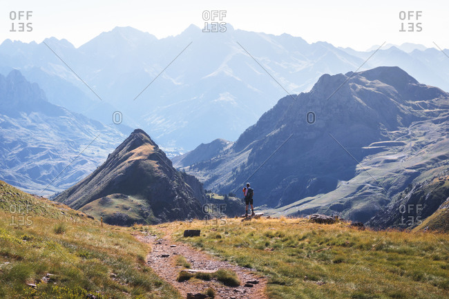 Back view of tourist standing on grassy hill and observing majestic scenery of mountain range on sunny day during vacation