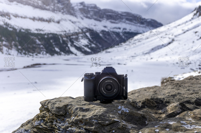Modern photo camera placed on stony ground against blurred mountain landscape with rocky slopes covered with snow in winter day