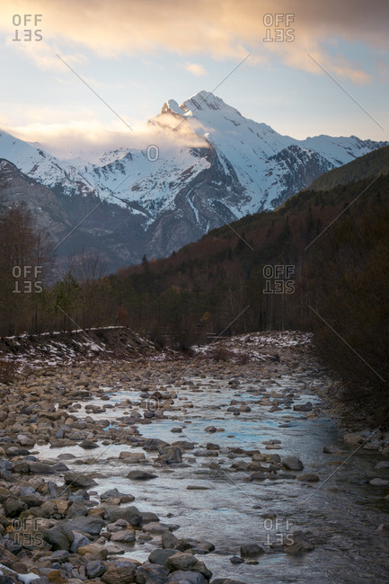Picturesque landscape of majestic mountain range with snow covered peaks and dark forest with shallow river flowing through valley