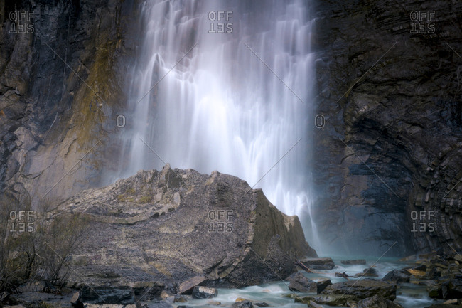 Amazing long exposure view of waterfall falling from steep cliff and splashing against rocky ravine
