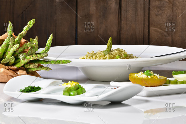 Delicious looking pasta dish with asparagus surrounded by plates with assorted vegetables. Healthy food concept..