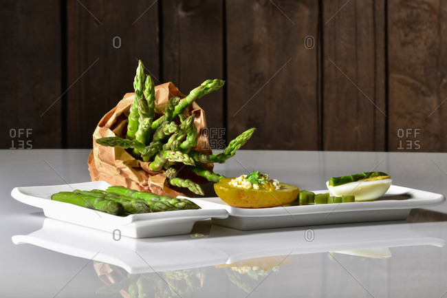 Assortment of plates with asparagus, half potato and half egg with a paper bag filled with fresh asparagus a on a table. Healthy food concept.