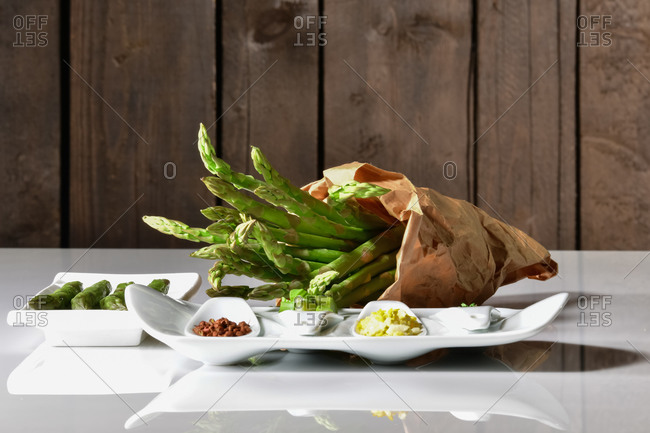 Paper bag filled with fresh asparagus surrounded by plates with more asparagus and assorted vegetables on a table. Healthy food concept.