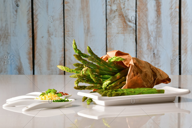 Assortment of plates with chopped vegetables and asparagus with a paper bag full of asparagus at the back on a table. Healthy food concept.