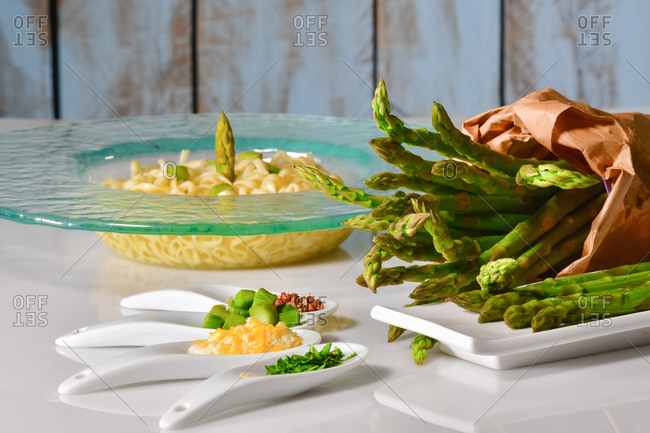 Close up of an assortment of plates with chopped vegetables and asparagus, with a paper bag filled with asparagus and a pasta dish at the back. Healthy food concept.