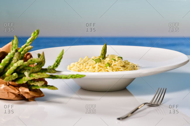 Close up of a tempting looking pasta dish with asparagus surrounded by an out of focus fork and fresh asparagus wrapped with paper. Healthy food and holidays concept.