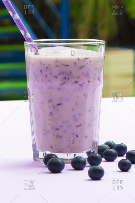 Tasty healthy blueberry smoothie served in glass with straws on table with fresh berries on purple background