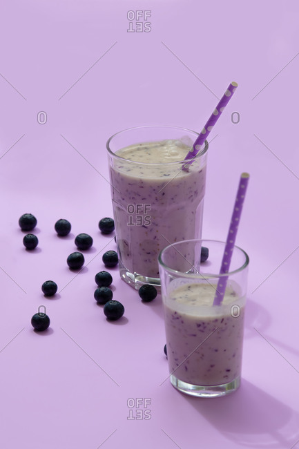 Tasty healthy blueberry smoothie served in glasses with straws on table with fresh berries on purple background