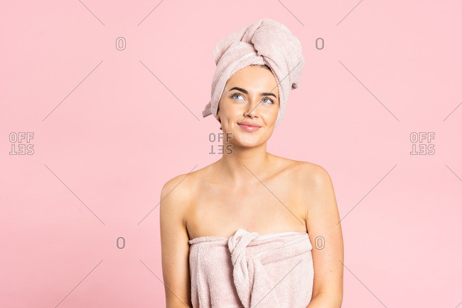 Delighted young bare shouldered female wrapped in towels smiling while enjoying healthy smooth skin after spa procedure on pink background