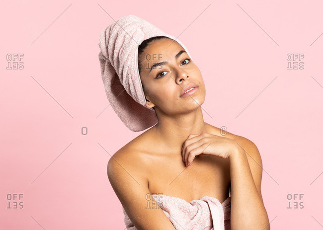 Charming young ethnic bare shouldered female with bath towel on head and perfect olive skin looking at camera against pink background while representing beauty and skincare concept