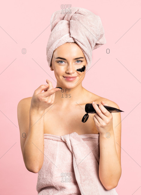 Young woman applying charcoal mask on face enjoying spa day while standing looking at camera on pink background