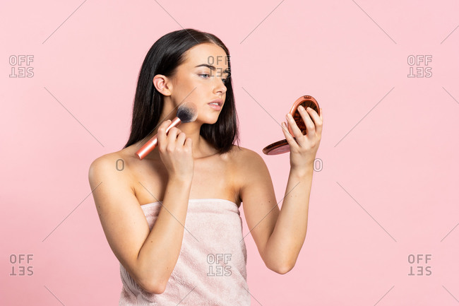 Young brunette woman doing makeup with brush while standing on pink background