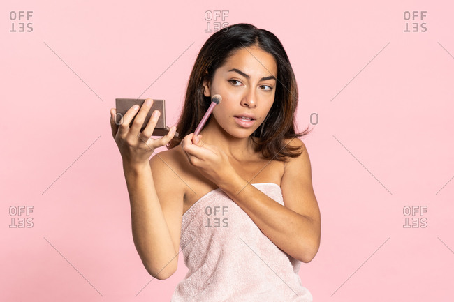 Young ethnic woman doing makeup with brush while standing on pink background