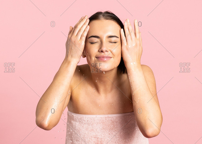 Woman wrapped in towel throwing herself water in the face with closed eyes while standing against pink background