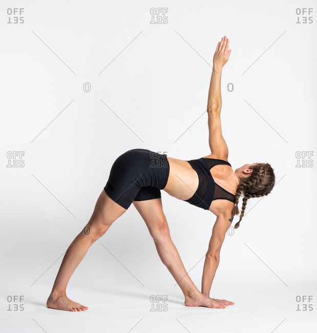 Full body side view of young barefoot female in sportswear performing Revolved Triangle yoga pose against white background