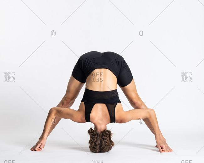 Full body of unrecognizable slim female in sportswear doing Wide Legged Forward Bend asana against white background