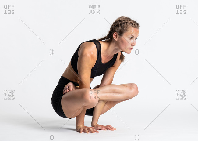Full body side view of concentrated young female in sportswear performing Scale yoga asana or Elevated Lotus pose against white background