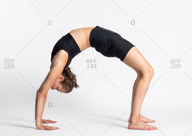 Full body side view of young slim female in sportswear performing advanced backbend Wheel yoga asana against white background