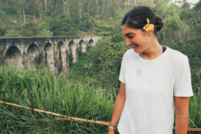 Smiling young ethnic female traveler with yellow flower in hair resting in green tropical forest near old arched bridge in Sri Lanka