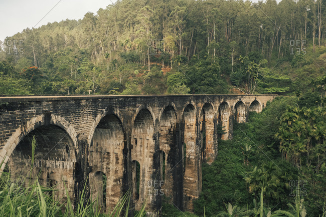 Colonial stone viaduct Nine Arch Bridge leading through green hilly terrain in Sri Lanka