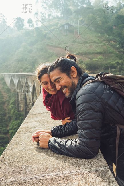 Side view of cheerful ethnic man and woman in activewear with backpacks talking and laughing while standing on aged stone Nine Arch Bridge among green hills in Sri Lanka