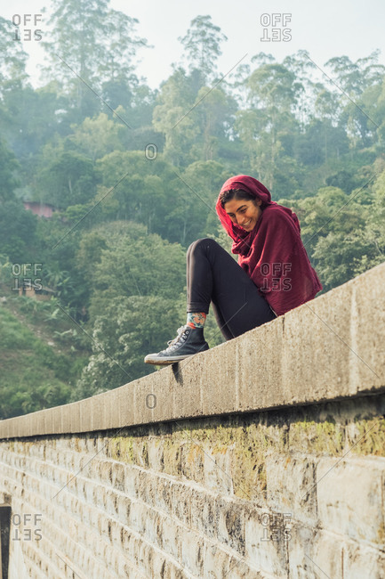 Low angle side view of cheerful young ethnic female traveler in active wear and headscarf sitting on stone border of aged bridge against green tropical foliage during vacation in Sri Lanka
