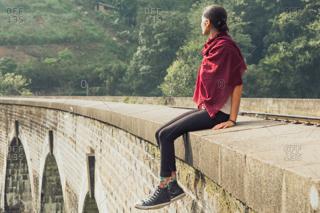 Low angle side view of thoughtful young ethnic female traveler in active wear and headscarf sitting on stone border of aged bridge against green tropical foliage during vacation in Sri Lanka