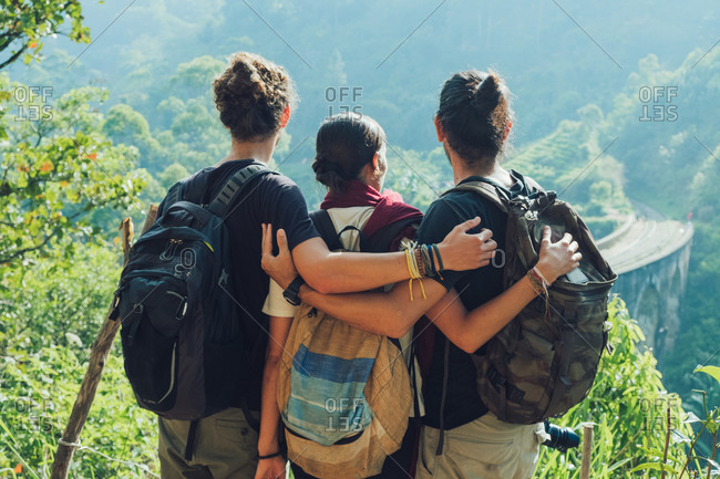 Back view of unrecognizable backpackers hugging each other while standing on green hill against old stone bridge and enjoying picturesque scenery during hiking in Sri Lanka