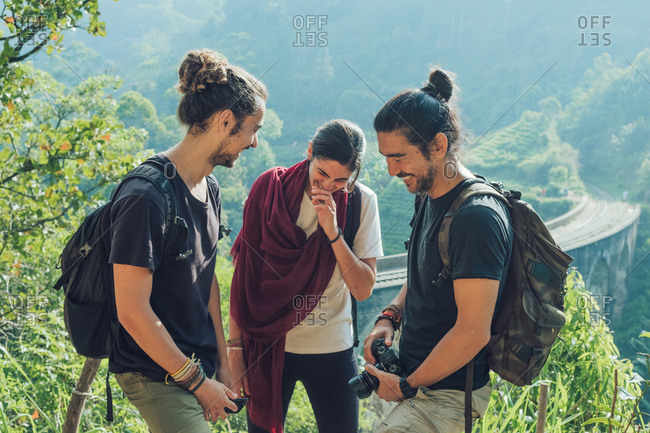 Group of cheerful young multiethnic friends with backpacks and photo camera having fun and laughing while standing on green hill near old viaduct bridge during summer holidays in Sri Lanka
