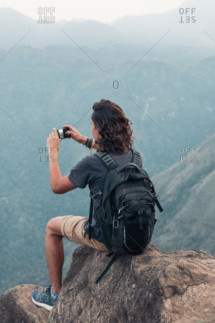 Side view of traveling male sitting on rock and taking picture on smartphone of amazing mountainous landscape in Sri Lanka