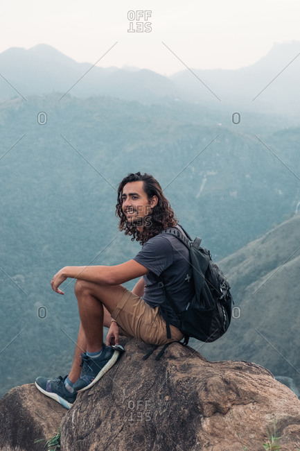 Content male traveler with backpack sitting on edge of rocky mountain on background of highlands in Sri Lanka and looking away during summer vacation