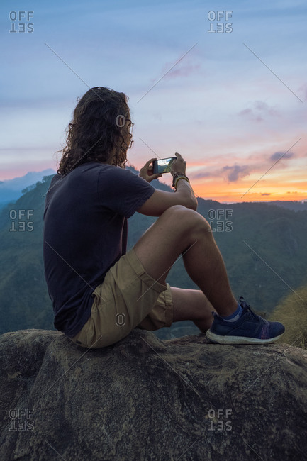Side view of traveling male sitting on rock and taking picture on smartphone of amazing mountainous landscape during sunset in Sri Lanka