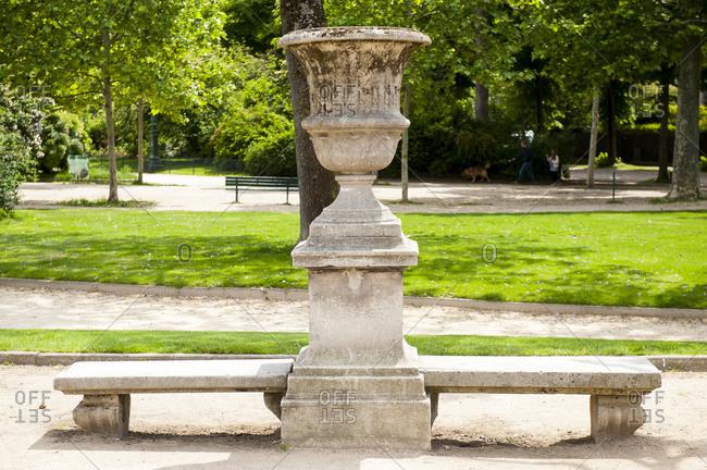 France - May 22,  2019: Uneven bench in Champ de Mars garden,  Paris,  France