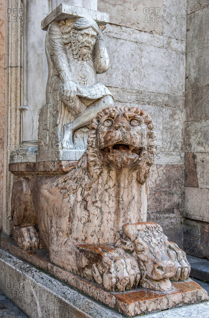 Italy - September 15,  2015: Italy,  Emilia-Romagna,  Ferrare, cathedral Saint Georges,  statue of lion in front of porch