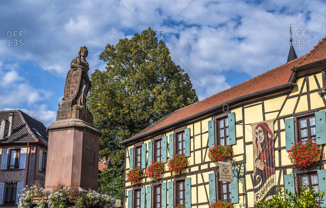 "France - September 22,  2019: France,  Alsace,  Wine Route,  Ribeauville,  fountain and hotel-restaurant ""du mouton"""