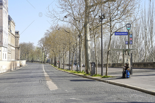 France - March 25,  2020: France,  Paris (1st arr.) 03/25/20. Homeless seated at a bus stop,  quai Francois Mitterrand completely empty following the confinement of the population to fight against the COVID-19 pandemic