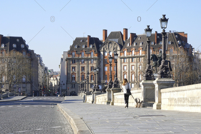 France - April 1,  2020: France,  Paris (1st arr.) 04/01/20. A single woman walks her dog on the empty Pont-Neuf following the confinement of the population to fight the COVID-19 pandemic