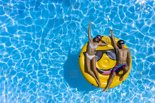 Young couple and smiley buoy at the pool