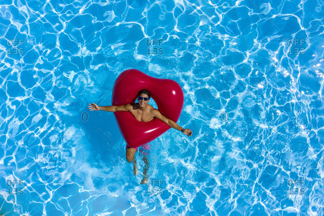 Young man at the pool with a red heart shaped buoy