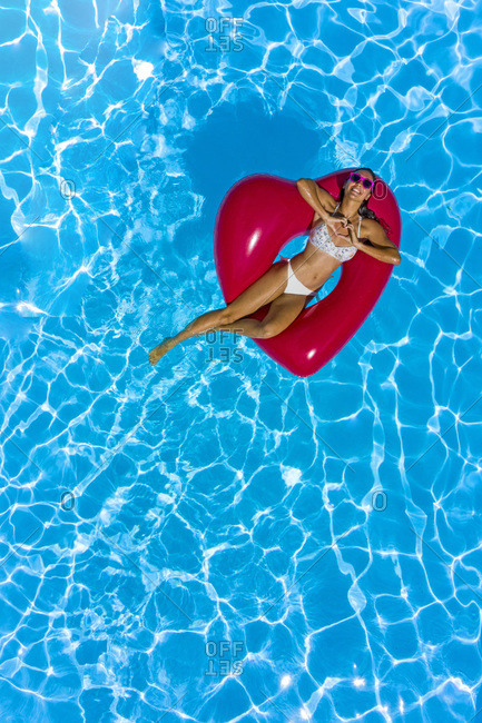 Young woman at the pool with a red heart shaped buoy