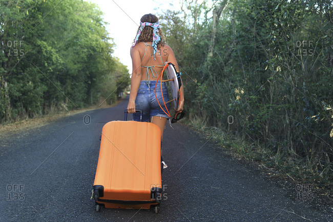 Girl with a suitcase. Young and Pretty Hippie on a Deserted Road