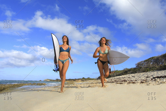 Two surfing girls on the beach