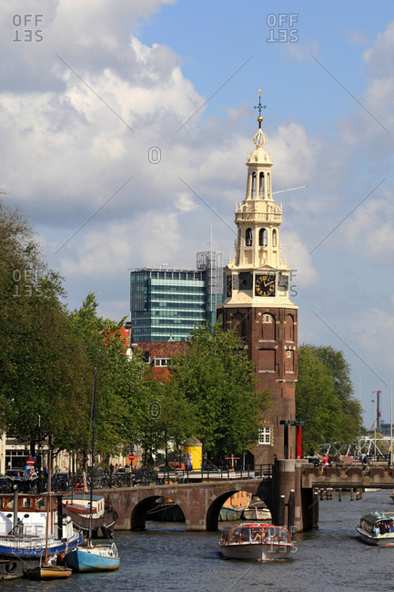 Netherlands - August 21,  2009: The Netherlands,  North Holland,  Amsterdam,  canal and Montelbaanstoren tower in the background