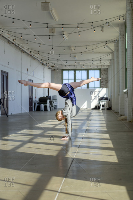 Teenage girl doing handstand and splits in dance studio